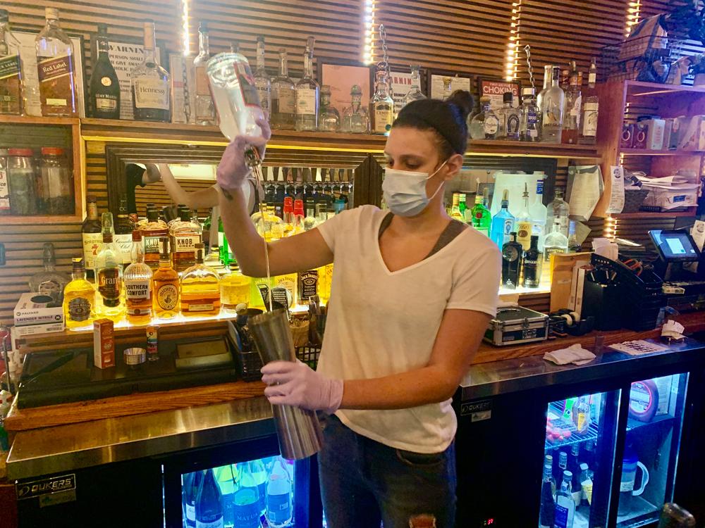 masked bartender opening a bar
